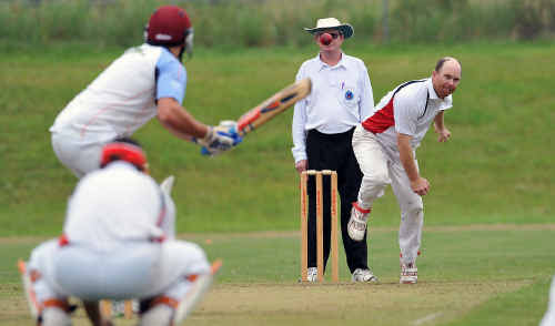 Colts bowler Andrew Firth bends his back as Tigers rival Scott Street awaits the ball.