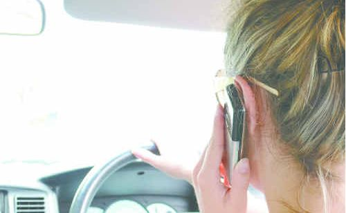 A driver with a mobile phone to her ear.
