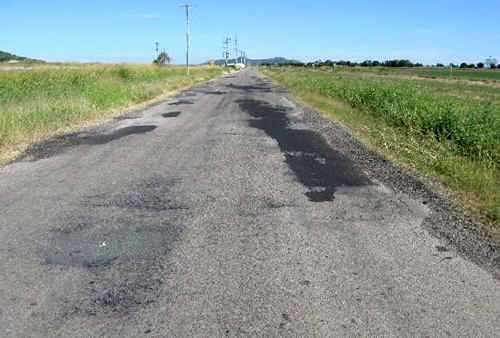 Patched potholes line Bootooloo Rd at Bowen. Roads damaged during last wet season we be repaired as part of a $91 million restoration program.
