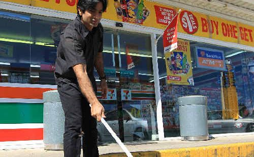 South Tweed 7-Eleven petrol station manager Amir Ishaq cleans up after his uninvited guests, the water beetles.
