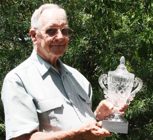 Springsure's Stan Priddle cradles one of the solid crystal trophies which would have been presented to race day winners.