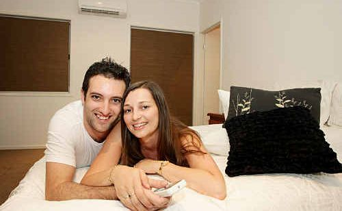 Michelle Gulliford and Robert Attard relax on the bed in the cool with their air conditioner on.