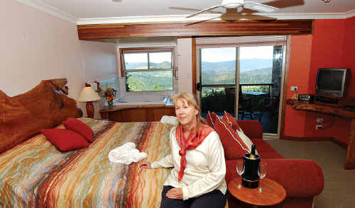 Maree DeGraw in one of her Maleny Artisan Spa Views suite overlooking the valley.