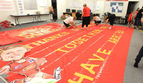 Gold Coast Suns supporters put the finishing touches to the huge banner.