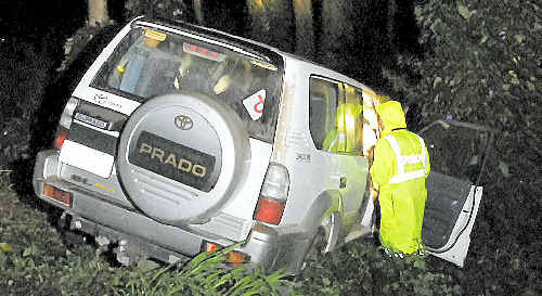Police inspect a Toyota Prado that rolled down Bridge St and into Jubilee Park.