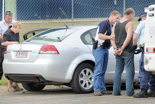 Hervey Bay police with two suspects after detaining a car with a boot full of copper wire at a business in Urangan.