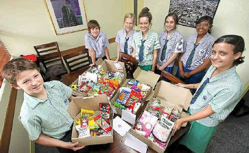 Year Nine TCC students, from left, Jack Hughes, Jack Nasser, Jade Reeves, Jasmine Hines, Catherine McKinnon, Shania Cora and Rochelle Hollingsworth hold up some of the packages they've put together for Australian troops serving in Afghanistan so they can enjoy Anzac Day.