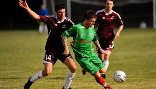 Daily Mercury Whitsunday Miners striker Jamie White shields the ball from a QAS player.