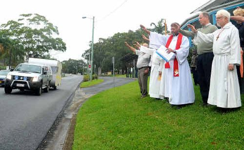 Father Ian Mabey, of St John's Anglican Church, Coffs Harbour, offering a Palm Sunday blessing to local roads yesterday.
