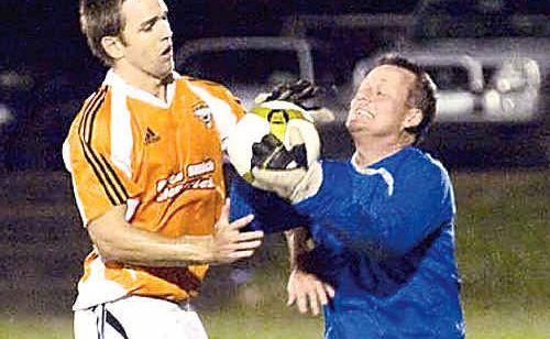 Wanderer's Mark Cavanagh and Kawana goalkeeper Jerry Finey contest the ball at Buderim.