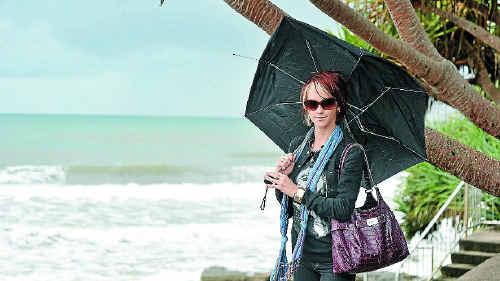 Jessie Macaulay checks out the surf as the rain tumbled down yesterday.
