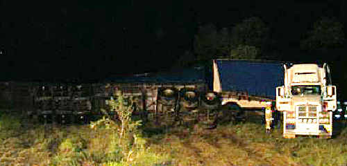Trailers of a prime mover that jack-knifed on the Capricorn Highway are rolled onto their side.
