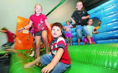 Cousins Ashley Collins, 11, and Mitchell Head, 3, enjoy their time on the jumping castle at The Crazy Joker with a group of their friends.