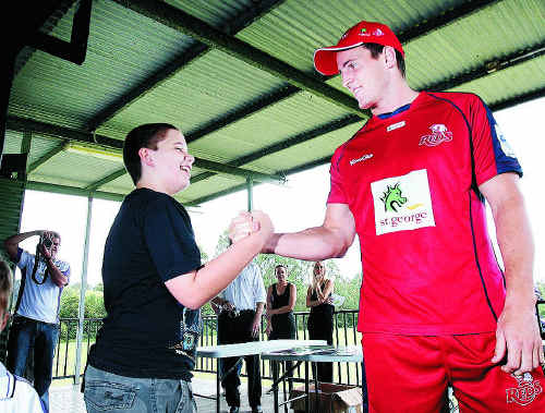 Queensland Reds player Mike Harris chats with a local youngster at the Lions Rugby Union Club in Karana Downs yesterday.
