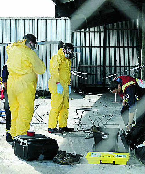 Hazmat officers prepare to re-enter the scene of the suspected drug lab at Billinudgel.