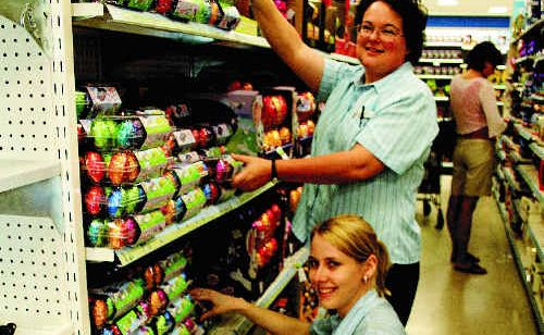 Big W staff members Julia Delange and Sarah Milwain are busy stocking shelves with easter eggs.