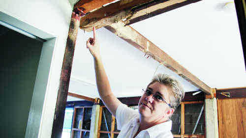 Robyn Swadek points to some termite damage inside her Ruby St home.