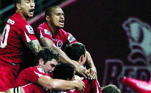 Reds players celebrate victory after the round 10 Super 15 match against the Waratahs at Suncorp Stadium.