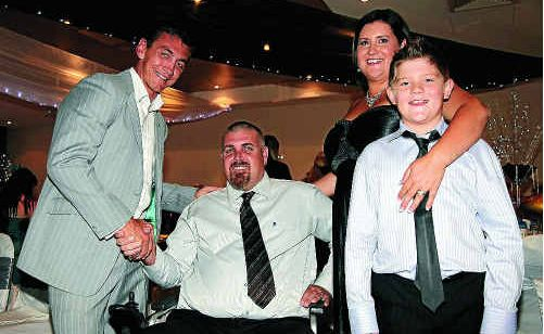 Mat Rogers supports motor neurone sufferer Graham Smith with his wife Aleiah Smith and son Mitchell at a fundraiser event.