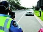 Senior Constable Tracy Round and Constable Geoffrey Steel keep watch for speedsters on a Rockhampton street.
