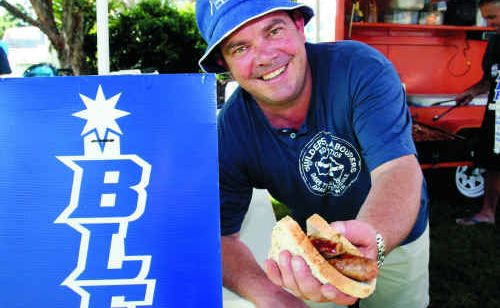 Dave Caldwell hands out sausage sandwiches at the Labour Day celebrations in Cotton Tree Park.