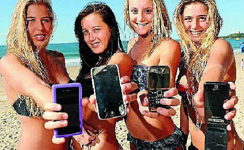 Tianni Hing, 16, Jasmin McDonald, 17, Madi Blackburn, 16, and Bronte Hartland, 16, keep their mobiles in hand.