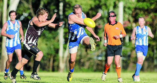 Brothers' Scott Smithwick gets his kick away despite the attention of a Panthers player during Saturday's match at Rockhampton Cricket Ground.
