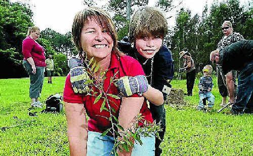Ethan Woods plants a tree with his mum Lisa Raith.