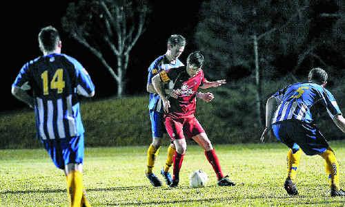 Kawana's Steve Conomos and NYU's Robert Lensen battle for control of the ball.