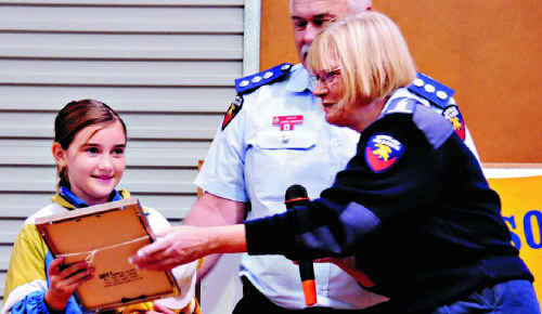Natalie Carr accepts an award from QFRS Communications Manager Moria Radel. Gympie Area Director Lloyd Johnston watches.