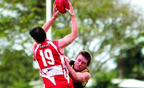 Eastern Swans' Jarrod Van Hees and Mackay City's John Macdonald leap for the mark.