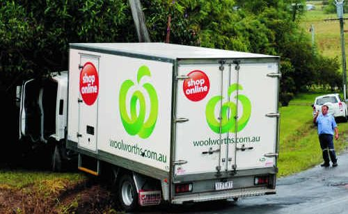 Emergency services assess the scene where a Woolworths supply truck is wedged against a power pole and leaking fuel on Glenview Rd.