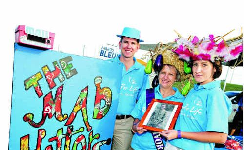 READY TO RELAY: The 2010 Mad Hatters team included Jarrod Bleijie, his mother Christine and Leah Stepto. They are holding a picture of Sgt Linden Bleijie, of the Australian ISF, their brother, son and partner, who was stationed in East Timor. The event did a live cross to him last year.