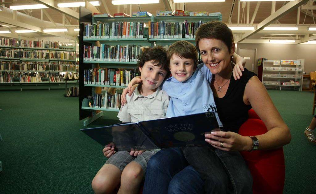 Oscar 8, Archie 5 and Angela Bueti reading some books at Kawana Library.