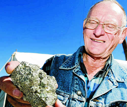 Tailgater Allen Campbell, of Brisbane, poses for a portrait, holding a chunk of iron pyrite, ahead of the  21st annual Lismore Gemfest at the Lismore Showgrounds.