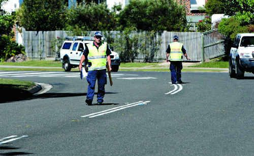 Forensic Crash Unit police officers investigate the scene of the fatal car crash on Golf Links Rd, Mountain Creek.