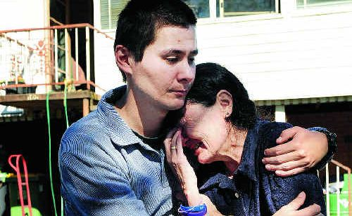 A distraught Christine Anderson is comforted by her son Geoff outside what was their family home of 20 years.