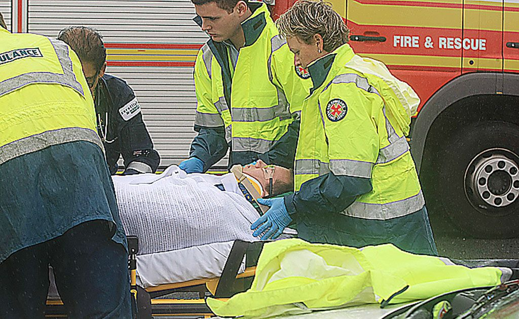 Emergency services personnel treat a man at the scene of an accident near the Tugun Bypass.