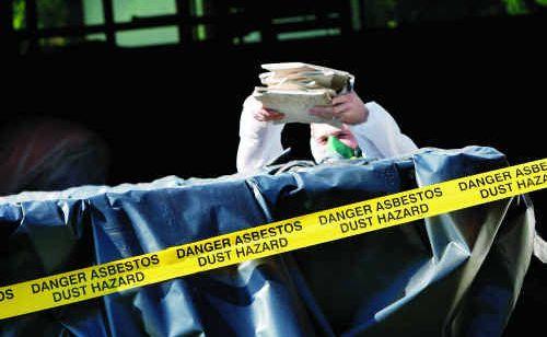 Contractors remove asbestos materials.
