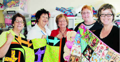 Lorna Hicks (centre) and the ladies from the Emerald Neighbourhood Centre displaying the donated hand-made quilts.