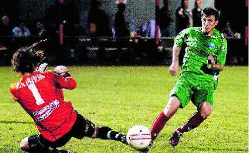 The Whitsunday Miners' Jamie White puts the ball past the FNQ Bulls goalie at Mareeba.