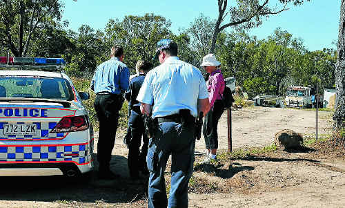 Police officers inspect a property after a man was arrested following a siege in Tannum Sands on Tuesday night.