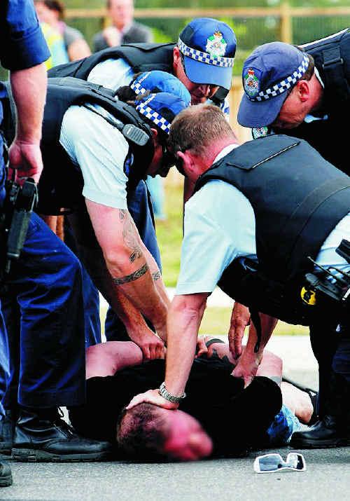 Police restrain the suspect.