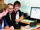 Mackay State High School student Steven Ruhle, deputy principal Cameron Wayman and student Lachlan Forsyth look at the school's new Facebook page..