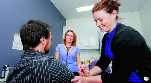 Dr Rachel Bidgood looks on as registered nurse Kelly Moscatt prepare to give a flu vaccination to a patient at Caneland Medical Centre.