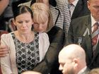 Inside the Gold Coast Convention Centre Sonya Leeding is comforted as the casket passes.