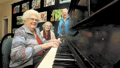 Clunes residents Gloria Francis (rear left) and Doris Armstrong watch as Connie Millett practises on the hall piano ahead of Saturday's centenary celebrations for the village's Coronation Hall.
