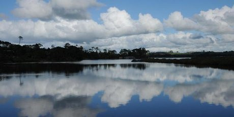 Fluffy clouds and sapphire sky are mirrored in Mangawhai's still, clear estuary.