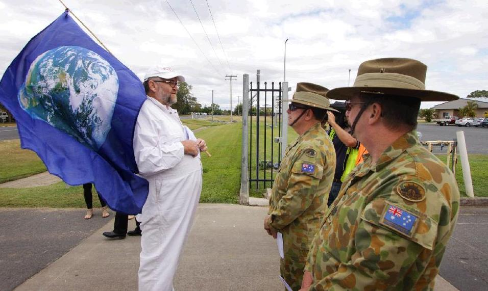 Protester Bryan Law stands outside the fenceline of Western Street Army Barracks, which is the staging area for Exercise Talisman Sabre. A new slogan was also unveiled on anti-war activist Graeme Dunstan's Peacebus.