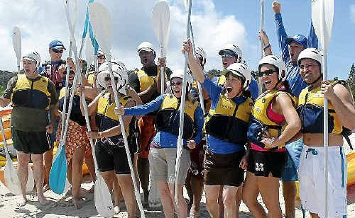Some of the 300 American audience members who accompanied Oprah Winfrey on her trip to Australia pose for the national media after taking to the sea in kayaks at Byron Bay's Main Beach.